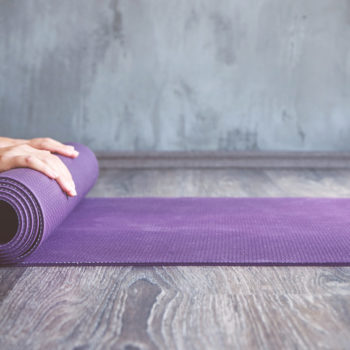 Woman rolling her mat after a yoga class